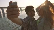 Romantic couple taking their photo near the bridge under sun rays Stock Footage