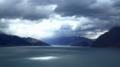 Cloudscape and mountain range with reflection of sunlight on water of Lake Stock Footage