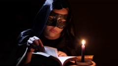 Wicca girl with a candle hails Satan and performing dark rituals. Halloween. 4K Stock Footage