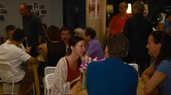Westerners talk and laugh at a table in juice bar Stock Footage