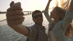 Beautiful couple taking self portrait using smartphone by the river Stock Footage
