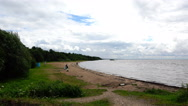 Single people sitting near the water at the beach on the sandy shore of the lake Stock Footage