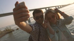 Romantic young couple smiling and taking their photo on smatphone Stock Footage
