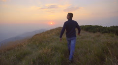 The man walk on the mountain against the background of sunset. Real time capture Stock Footage