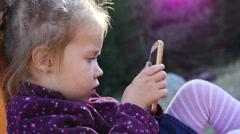 Little child girl portrait sit in park playground type slide watch smart phone Stock Footage