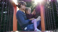 Mother with little child girl sit park playground type slide watch smart phone Stock Footage