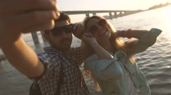 Harmonious young couple taking selfies on the beach against shining sun Stock Footage