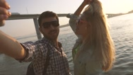 Passionate couple smiling and kissing whole taking photo of themselves at sunset Stock Footage