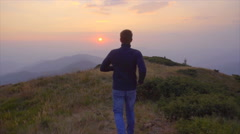 The man run in the mountain on the background of the sunset. Slow motion Stock Footage