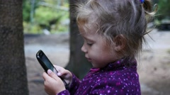 Little child girl portrait in forest nature park type slide watch smart phone Stock Footage