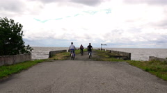 Young athletes at the two bikes I stop on the lake dock in windy weather Stock Footage