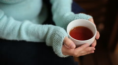 Girl in a blue sweater sitting on a wooden chair and drinking tea Stock Footage