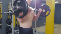 Muscular man working out in gym doing exercises with barbell at biceps Stock Footage
