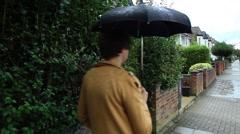 Girl in a yellow coat walking in the rain. Stock Footage