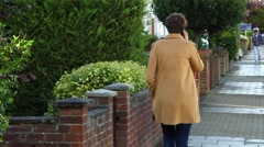 Girl in a yellow coat goes along the street and talking on the phone. Stock Footage