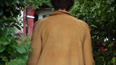 Girl in a yellow coat passes through the garden to the house. Stock Footage