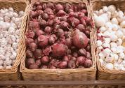 Bunch of red onion, white onion and garlic in wicker tray in supermarket Stock Photos
