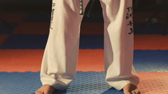 Martial taekwondo arts athlete tying the knot to his black belt in the gym Stock Footage