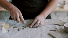 Girl cuts triangles of clay Stock Footage
