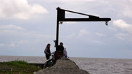 The young men and the girl sit on Stone quay near the bike talking Stock Footage