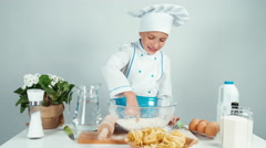 Young baker playing with flour at bowl at kitchen table and smiling at camera Stock Footage