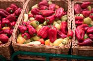 Bunch of red and yellow paprika peppers in wicker boxes in supermarket Stock Photos