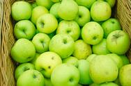 Fresh green apples in wicker tray of a supermarket Stock Photos