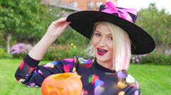 Young woman wearing witch hat and with jack latern on Halloween party Stock Footage