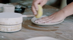 Girl is polish clay plate Stock Footage