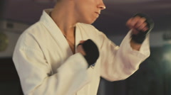 Kickboxer in the robe training taekwondo with punching bag in the gym Stock Footage