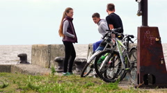 Athletic young healthy people sit on the rocks in an empty and cold quay near Stock Footage