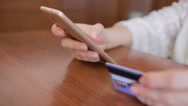 Woman makes a purchase using a smartphone and a bank card. Stock Footage