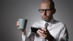 Elegant businessman in white shirt holding a cup of coffee or tea in hands. The Stock Footage