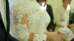 Wedding ceremony in orthodox church. Bride and groom holding the candles. Close Stock Footage