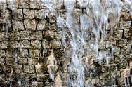Artificial waterfall. Water stream fall down in front of ancient brick wall Stock Photos