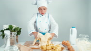 Young baker girl making dough at the kitchen table Stock Footage