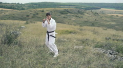 Sportsman exercising moves of taekwondo on the nature. Slowly Stock Footage