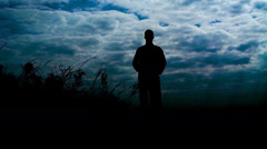 Silhouete of man stands on the stone rock with raised arms in windy day. Slowly Stock Footage