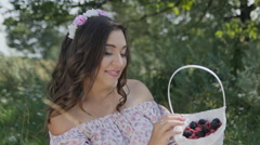 Beautiful Girl with a Wreath of Flowers on her Head Shows Berry BlackBerry and E Stock Footage