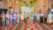 Little children stand and clap in the auditorium Stock Footage