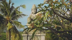 Stone hindu statue from behind frangipani tree, slide Stock Footage