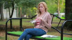 Blond girl in a park eating a donut. Woman outdoors chews sweet bun Stock Footage