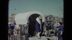 1960: middle-aged woman exiting desert tourist attraction covered wagon  Stock Footage
