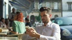 Handsome man looking absorbed while browsing internet on smartphone Stock Footage