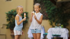Adorable little girls eating ice-cream outdoors at summer. Cute kids enjoying Arkistovideo