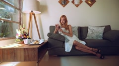 Young woman in white dress having ice coffee on a couch, slide Stock Footage
