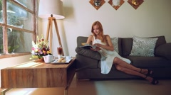 Young woman in white dress reading magazine on a couch, slide Stock Footage