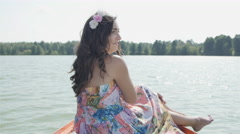 Girl Sitting on the bow of the Boat and Smiles for the Camera Stock Footage