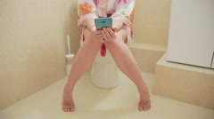 Woman sitting on toilet in the bathroom. using smartphone. home bathrobe Stock Footage