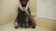 Woman sitting on toilet in the bathroom. using smartphone. Evening Dress Stock Footage